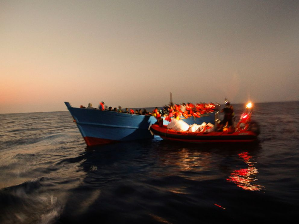 PHOTO: Migrants sailing in a crowded wooden boat carrying more than seven hundred migrants, are helped by members of an NGO during a rescue operation at the Mediterranean sea, about 13 miles north of Sabratha, Libya, Aug. 29, 2016.