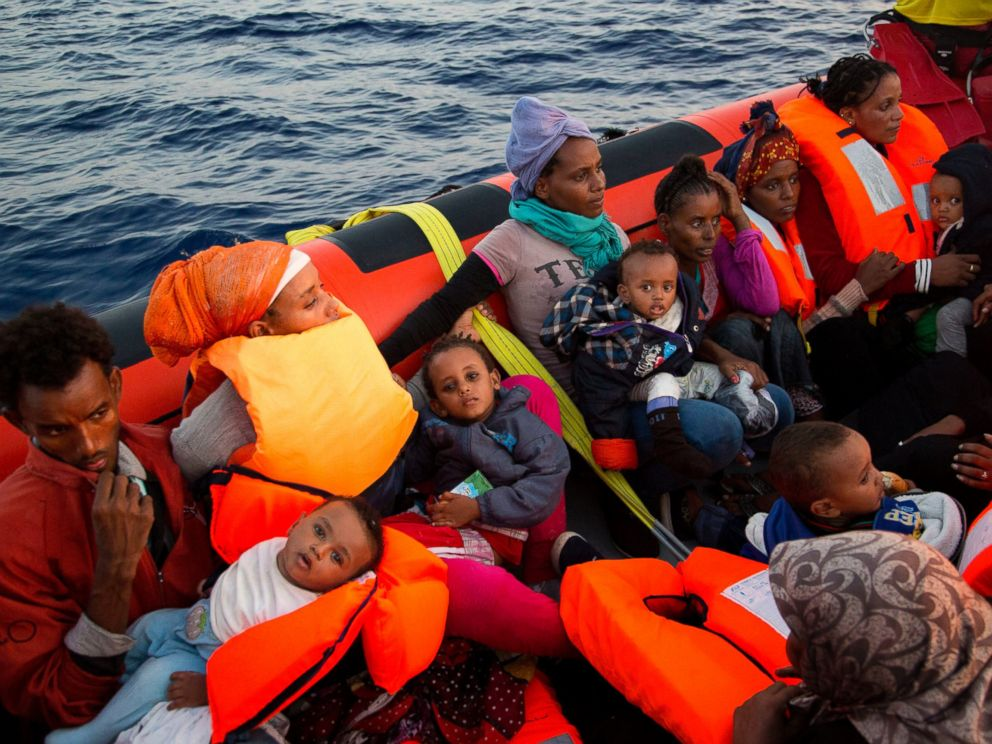 PHOTO: Migrants from Eritrea hold their children after been rescued from a crowded wooden boat as they were fleeing Libya, about 13 miles north of Sabratha, Libya, Aug. 29, 2016.