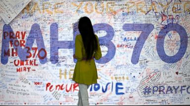 PHOTO: A woman reads messages and well wishes to people involved with the missing Malaysia Airlines jetliner MH370, Saturday, March 15, 2014 in Sepang, Malaysia.