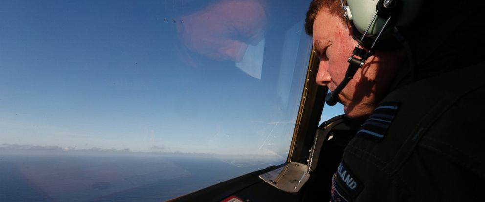 PHOTO: Royal New Zealand Air Force P-3K2 Orion co-pilot Brett McKenzie looks out from the cockpit for the missing Malaysian Airlines flight 370 over the southern Indian Ocean, Saturday, March 29, 2014.