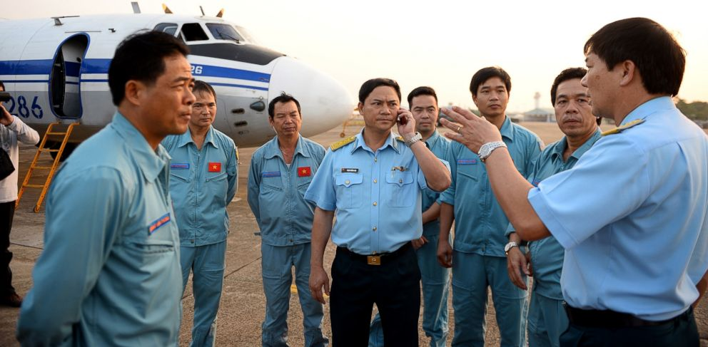 PHOTO: Vietnamese air force crew stand in front of a plane at Tan Son Nhat airport in Ho Chi Minh City, Vietnam on Sunday March 9, 2014 before heading out to the sea area between Vietnam and Malaysia where a Malaysian airliner vanished March 8, 2014.