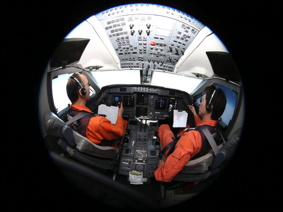 PHOTO: Captain of the Japan Coast Guard Gulfstream Makoto Hoshi, left, and his co-pilot Shunichi Yumiza sit in the cockpit during a search for the missing Malaysia Airlines Flight MH370 in the Southern Indian Ocean, near Australia, April 1, 2014.