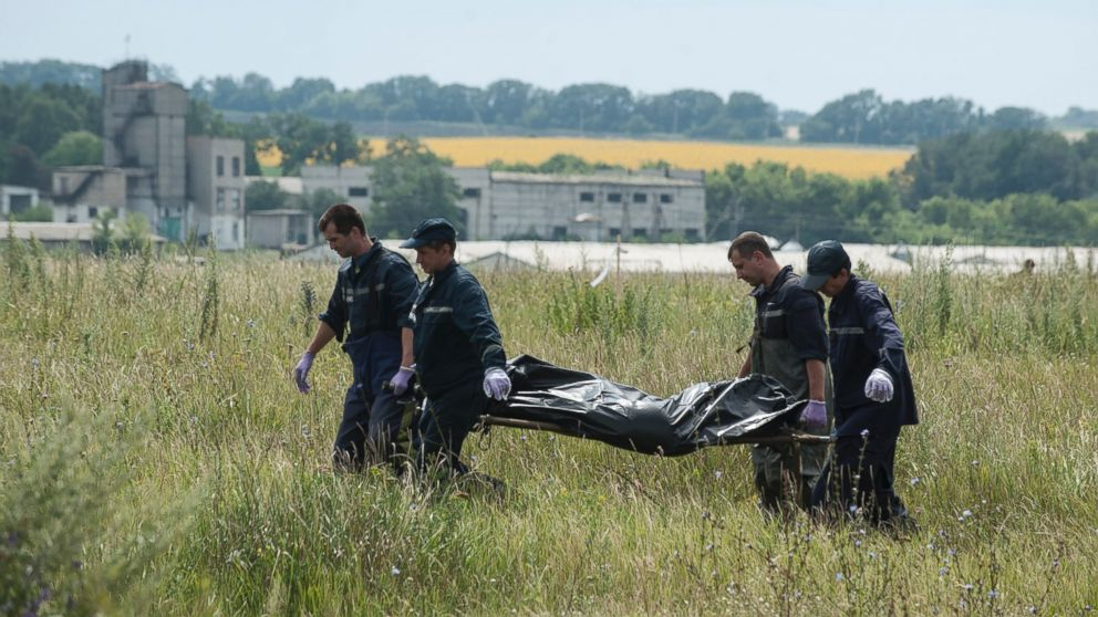 PHOTO: Rescue workers carry a plastic bag with a dead body at the crash site of a Malaysia Airlines jet near the village of Hrabove, eastern Ukraine, Saturday, July 19, 2014.