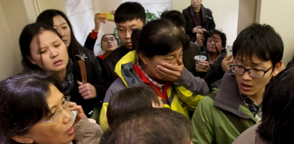 PHOTO: A woman, center, surrounded by media covers her mouth on her arrival at a hotel which is prepared for relatives or friends of passengers aboard a missing airline, in Beijing, China Saturday, March 8, 2014.