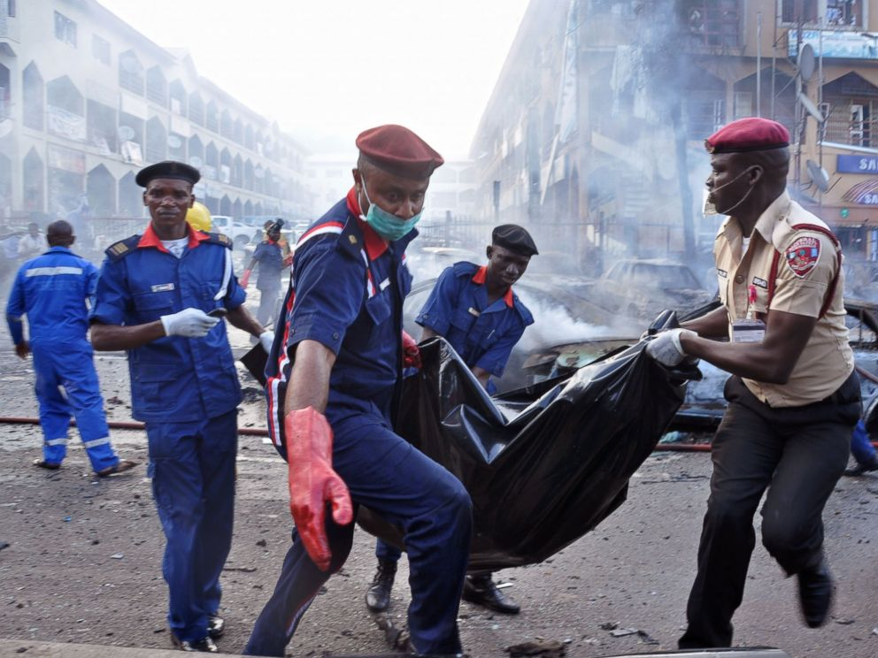 PHOTO: Rescue workers carry a body bag after a explosion at a shopping mall in Abuja, Nigeria