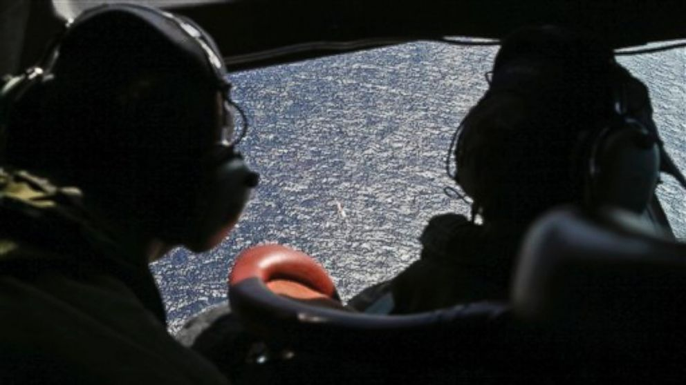 PHOTO: Wing commander Rob Shearer captain of the Royal New Zealand Air Force P3 Orion left, and Sgt. Sean Donaldson look out the cockpit windows during search operations for