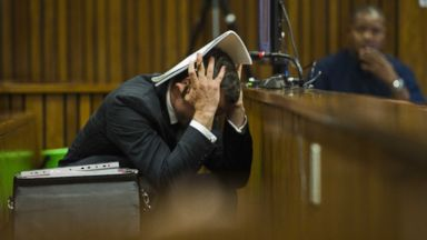 PHOTO: Oscar Pistorius covers his head with his hands and a notebook