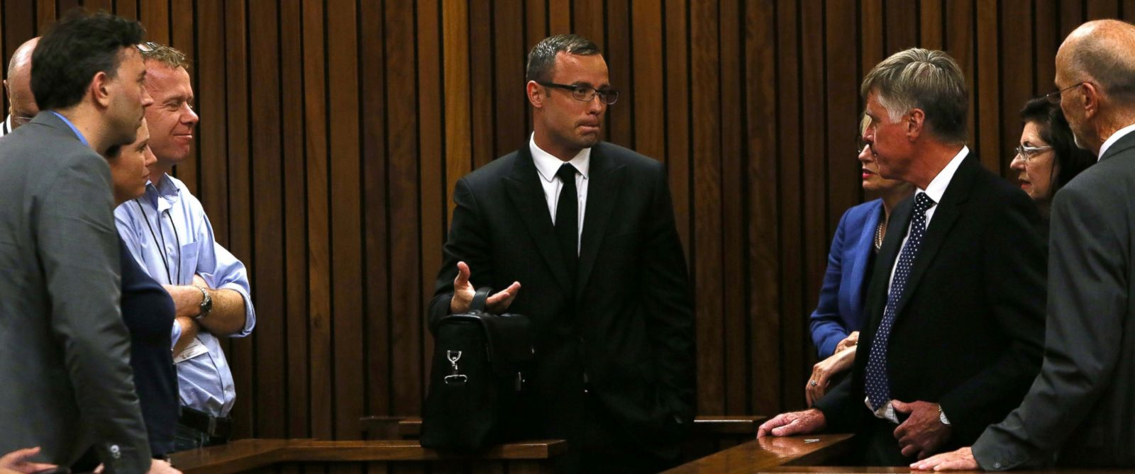 PHOTO: Oscar Pistorius, speaks with family and friends at right as press look on, March 25, 2014 in Pretoria, South Africa.