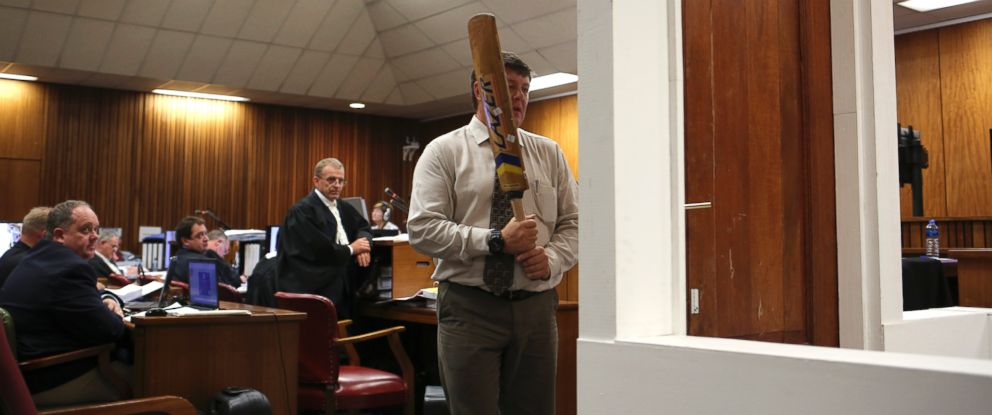 PHOTO: Forensic investigator Johannes Vermeulen is pictured with a cricket bat, demonstrating on a mock-up toilet and door details of how the door could have been broken down, in Pretoria, South Africa on March 12, 2014.