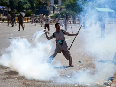 PHOTO: A Pakistani protester throws tear gas shell back towards police during a protest in Islamabad, Pakistan, Aug. 31, 2014.