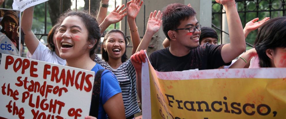 "PHOTO: Youth and students shout ""Welcome Pope Francis"" after throwing colored powder in the air at the start of the countdown to welcome the Pontiff, Jan. 14, 2015 in Manila, Philippines."