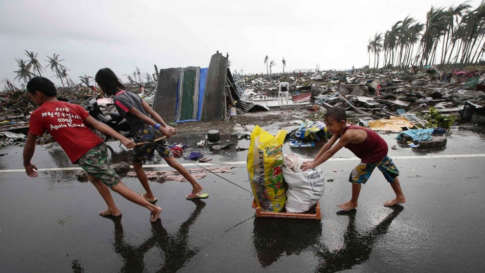 PHOTO: Residents carry relief goods past damaged homes in Tacloban city, Leyte province, central Philippines on Sunday, Nov. 10, 2013.