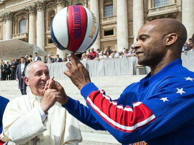 PHOTO: Harlem Globetrotters Flight Time Lang, right, helps Pope Francis spin the ball on his finger as they meet during the general audience in St. Peters Square at the Vatican, May 6, 2015.