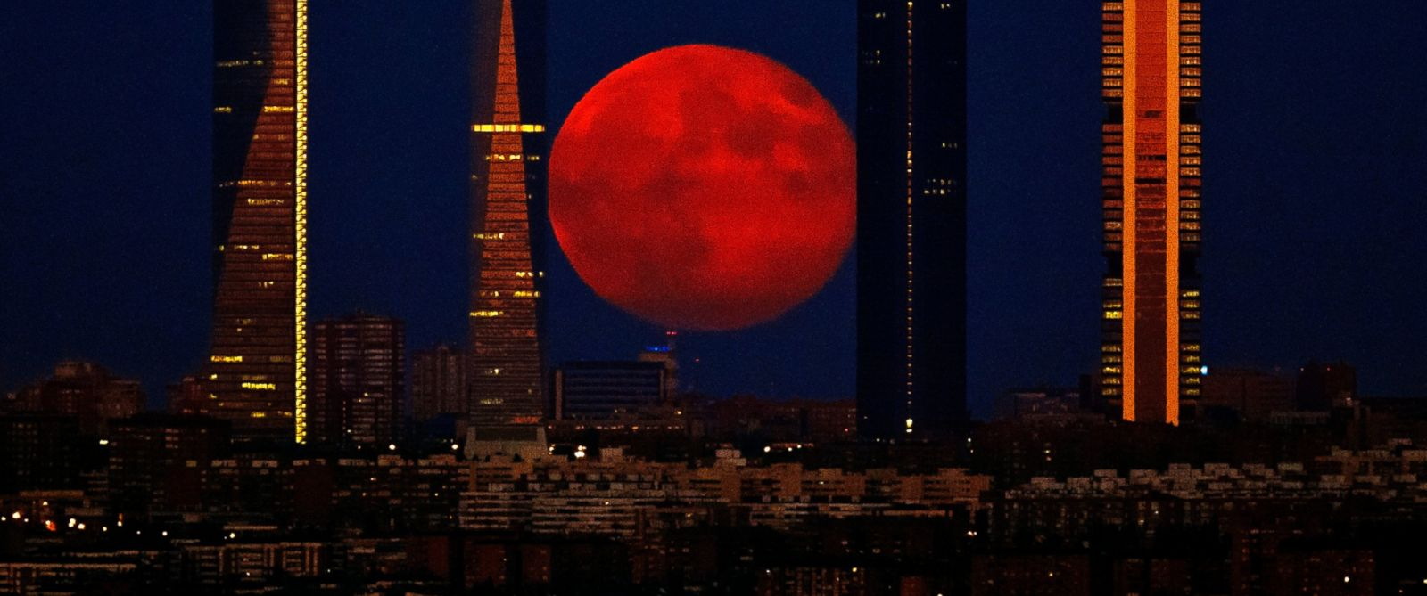 PHOTO: The moon rises in the sky as seen through the Four Towers, or Cuatro Torres Business Area, in Madrid, Spain on Aug. 11, 2014.