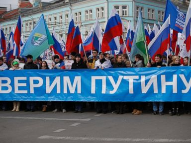 PHOTO: Demonstrators hold Russian flags and a poster We trust Putin during a demonstration in support of Kremlin-backed plans for the Ukrainian province of Crimea to break away and merge with Russia, in Moscow, Saturday, March 15, 2014.