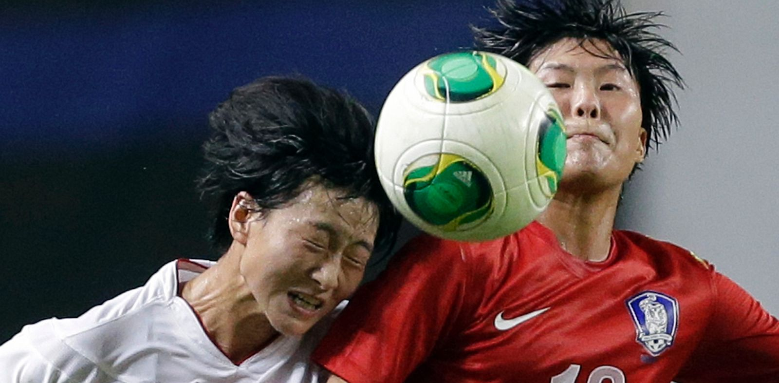 PHOTO: South Koreas Ji So-yun, right, fights for the ball against North Koreas Kim Un Hyang during their Womens East Asian Cup soccer match at Seoul World Cup stadium in Seoul, South Korea, Sunday, July 21, 2013. North Korea won 2-1.