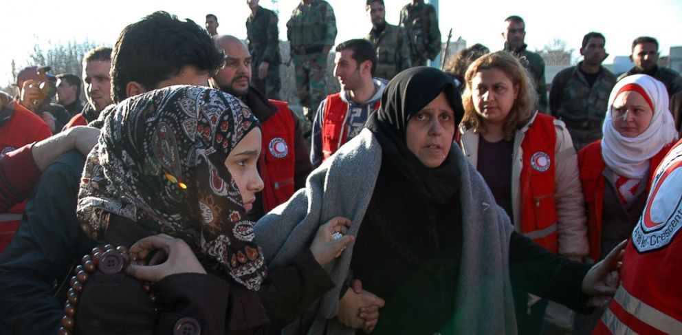 PHOTO: Syrian army soldiers look on as women walk towards a bus to evacuate the battleground city of Homs, Syria, Feb. 9, 2014.