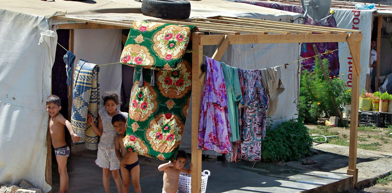 PHOTO: Syrian refugee children stand outside their tent at a temporary refugee camp in the eastern Lebanese town of Faour near the border with Syria, Lebanon, Aug. 28, 2013.