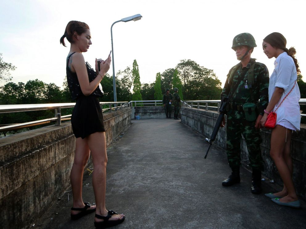 PHOTO: Passers by take photograph with a Thai soldier guarding a pedestrian overfly near the site where pro-government demonstrators stage a rally on the outskirts of Bangkok, May 20, 2014.