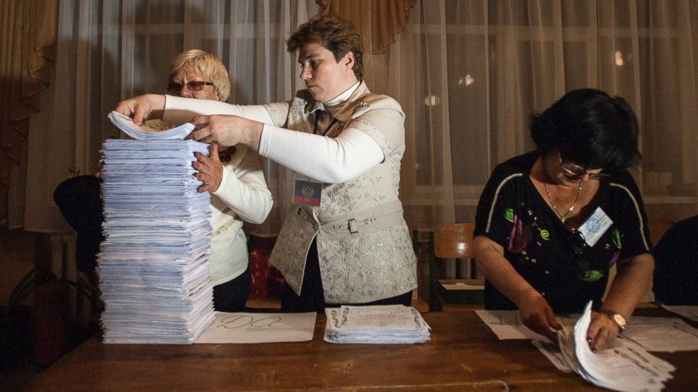 PHOTO: Members of the election committee empty a ballot box after voting closed at a pol
