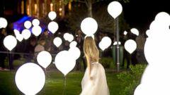 PHOTO: A woman walks between balloons part of an art light installation in Bucharest, Romania, April 23, 2015.