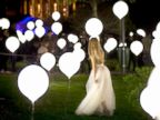 PHOTO: A woman walks between balloons part of an art light installation in Bucharest, Romania, April 23, 2015.