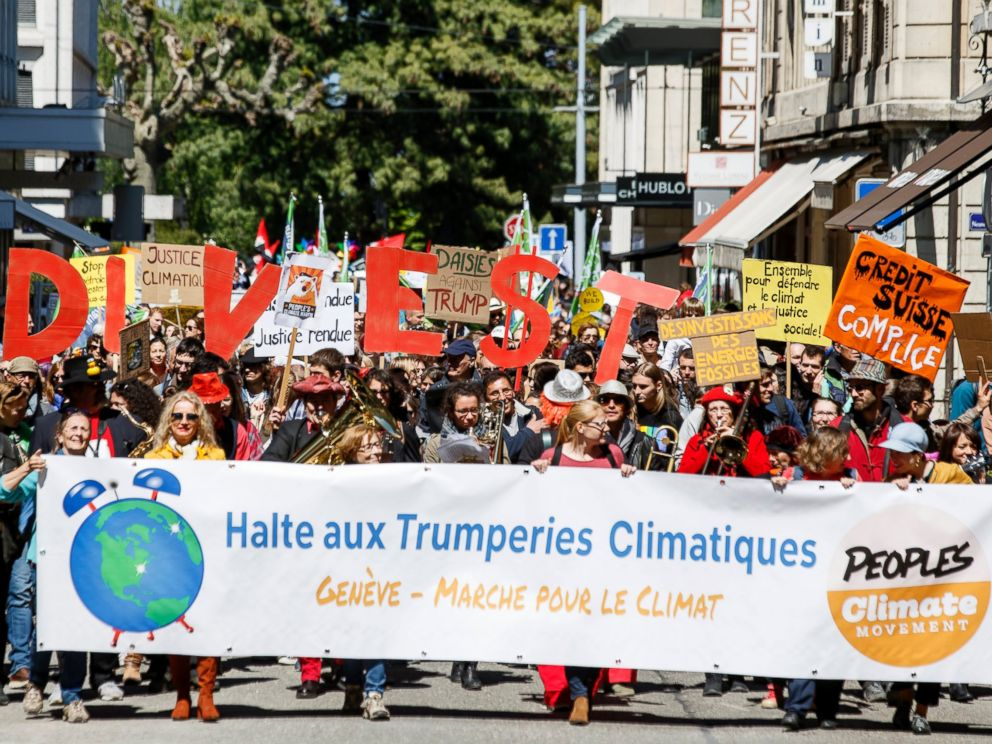PHOTO: About five hundred protesters hold placards reading, Stop climactic Trumperies during the World Climate March in Geneva, Switzerland, April 29, 2017.