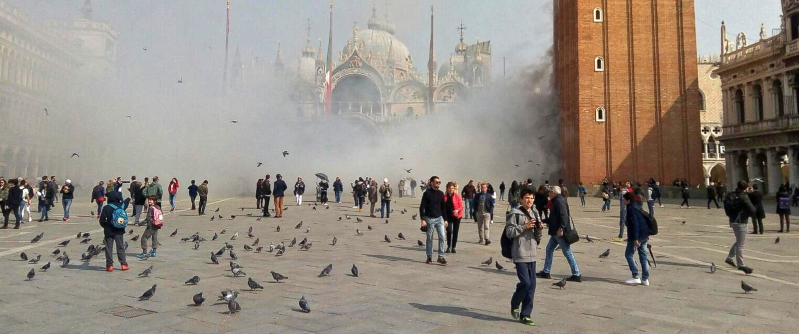 PHOTO: People walk in St Marks square as a smoke bomb is launched during an attempted robbery, in Venice, Italy, March 17, 2017.