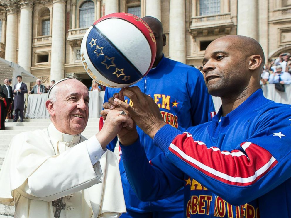 PHOTO: Harlem Globetrotters' help Pope Francis spin the ball on his finger as they meet during the general audience in St. Peters Square at the Vatican, May 6, 2015