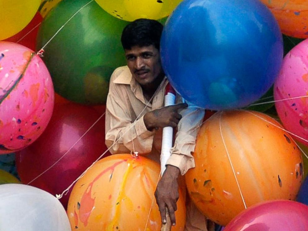 PHOTO: A Pakistani man sells colorful balloons as he waits for customers during the Eid al-Fitr celebrations, in Karachi, Pakistan, July 19, 2014.