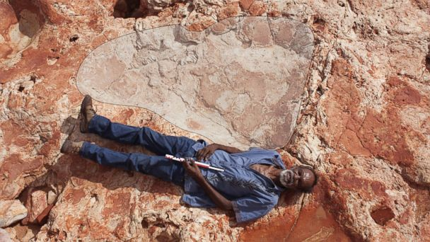 PHOTO: Richard Hunter posing for a photograph with the world's biggest dinosaur footprint, a 5 feet 9 inches sauropod track discovered in Western Australia.