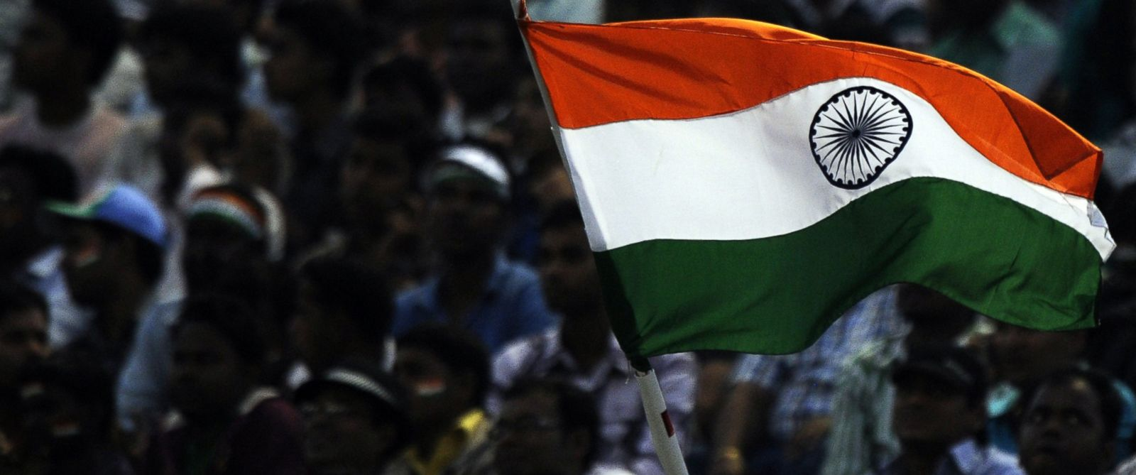 PHOTO: Indian cricket fans celebrate as they wave their national flag during the first One Day International (ODI) match between Indian and West Indies at the Barabati Stadium in Cuttack, on Nov. 29, 2011.