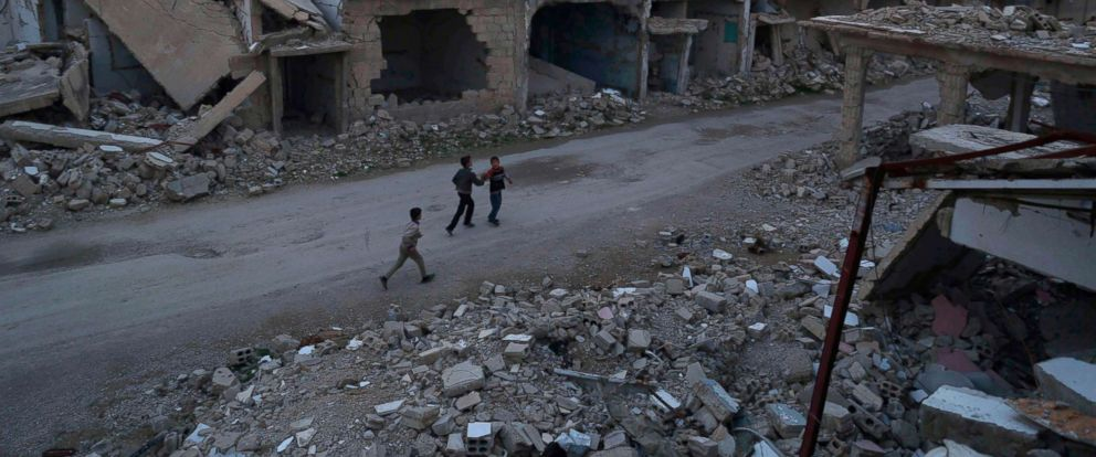 PHOTO: Syrian children walk past heavily damaged buildings in the rebel-held town of Douma, on the eastern edges of the capital Damascus, on Feb. 27, 2016, on the first day of the landmark ceasefire agreement.