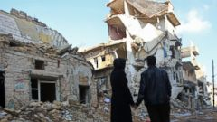 PHOTO: Kefa Jawish and her husband Tajeddin Ahmed look a destroyed building in the Aleppos northeastern Haydariya neighbourhood as they head to check their house for the first time in four years, Dec. 4, 2016.