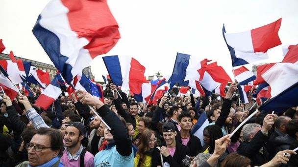 PHOTO: Supporters of French presidential election candidate for the En Marche ! movement Emmanuel Macron wave French national flags as they celebrate in front of the Pyramid at the Louvre Museum in Paris, May 7, 2017.