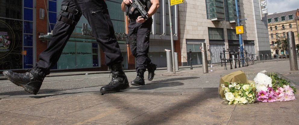 PHOTO: Armed police patrol Shudehill as they walk past floral tributes to victims, May 23, 2017, in Manchester, England.