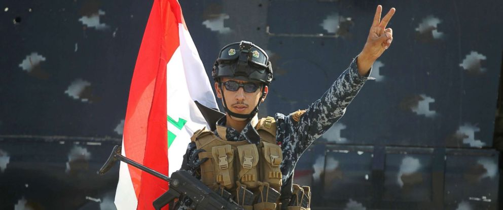 """PHOTO: An Iraqi federal police member flashes the sign for victory as he celebrates in the Old City of Mosul, July 9, 2017 after the governments announcement of the """"liberation"""" of the embattled city."""