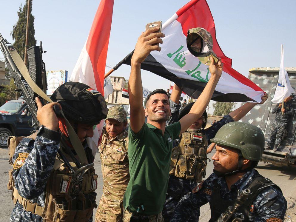 PHOTO: An Iraqi man takes a selfie with federal police members as they celebrate in the Old City of Mosul on July 9, 2017 after the governments announcement of the liberation of the embattled city.