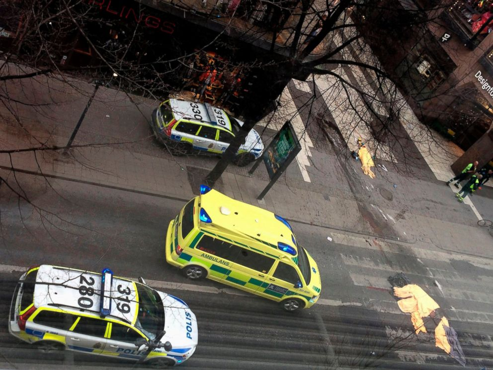 PHOTO: An ambulance stands near covered bodies at the scene where a truck crashed into the Ahlens department store at Drottninggatan in central Stockholm, April 7, 2017.