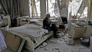 PHOTO: Mohammad Mohiedine Anis, 70, smokes his pipe as he sits in his destroyed bedroom listening to music on his vinyl player in Aleppos formerly rebel-held al-Shaar neighborhood.