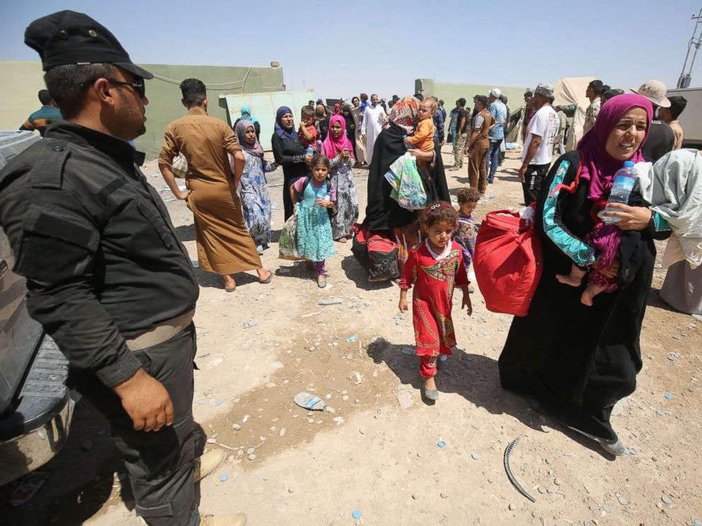 PHOTO: Iraqi security keep watch as civilians arrive on July 27, 2016, at a camp for displaced people in the district of Hajaj after fleeing the towns of al-Shirqat and Qayyarah, south of the city of Mosul.