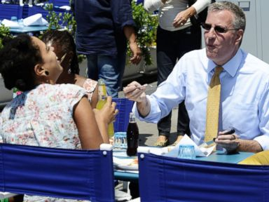 PHOTO: The mayor of New York City, Bill de Blasio, his wife Chirlane McCray (hidden) and their children Dante and Chiara eat pizza in a pizzeria in Naples, Italy, July 23, 2014.