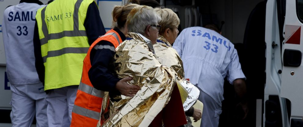 Emergency services personnel escort people away from the site of a deadly collision on October 23, 2015 in Puisseguin, southwestern France.