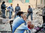 PHOTO: Victims sit among the rubble of a house after a strong earthquake hit Amatrice on August 24, 2016.