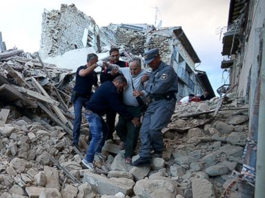 PHOTO: Residents and rescuers help a man among the rubble after a strong earthquake hit Amatrice on August 24, 2016
