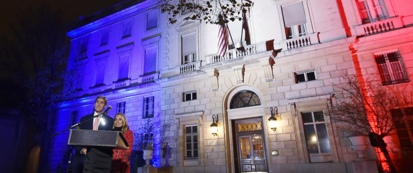 PHOTO: US Secretary of State John Kerry, next to US ambassador to France Jane D. Hartley, delivers a speech at the US embassy illuminated with the colors of the French national flag on Nov. 16, 2015 in Paris.