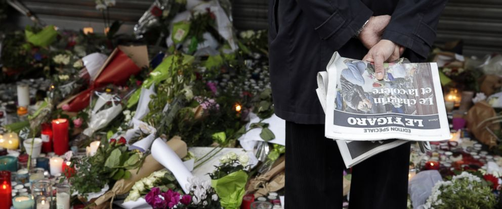 PHOTO: Flowers and candles are placed outside the La Belle Equipe restaurant along the Rue de Charonne in central east Paris, on November 15, 2015, two days after deadly attacks across the city.