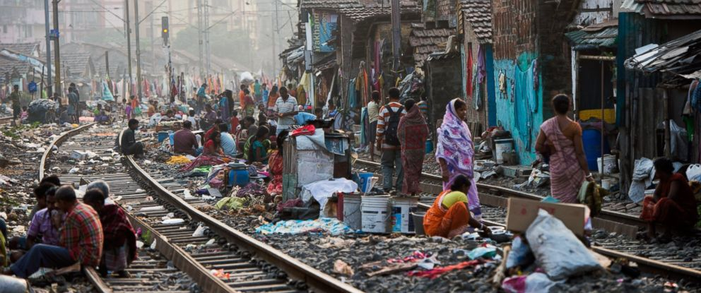 PHOTO: People get on with their lives in a slum on the railway tracks as a commuter train goes past on Dec. 12, 2013 in Kolkata, India.