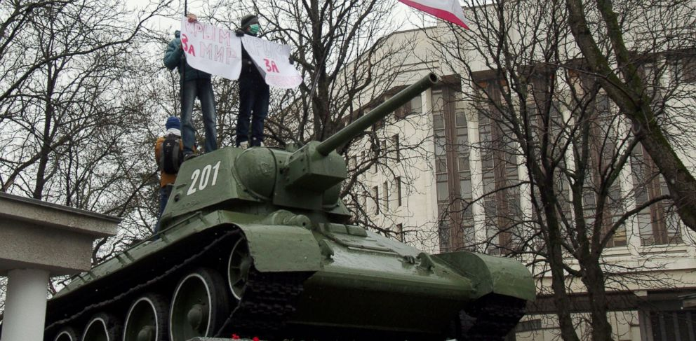 "PHOTO: Pro-Russian demonstrators hold placards reading ""Crimea for peace"" as they stand on a T-34 Soviet tank, set as a WWII monument in front of the Crimean parliament in Simferopol, Feb. 27, 2014."