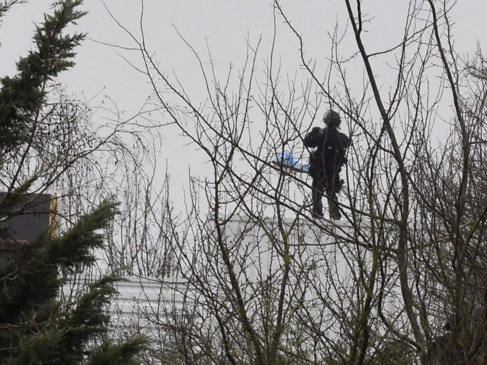PHOTO: A French police officer stands on the roof where two suspects in a France massacre are believed to be holed up, Jan. 9 ,2015, in the village of Dammartin-en-Goele, Northeast of Paris.